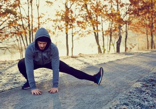 Male runner doing stretching exercise preparing for morning running workout in the park during sunny and cold fall